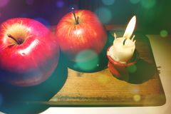 Christmas composition with red apples and tiny burnt down candle. royalty free stock photography