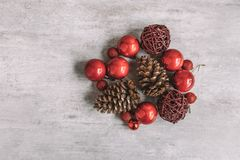 Christmas composition with red baubles and pine cones on wooden royalty free stock images