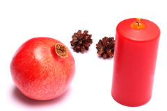 Christmas composition with red candle and pomegranate Stock Image