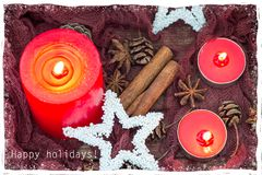 Christmas composition with with red candles, stars, winter spices and cones. Snowy frame and happy holidays text. Christmas composition with with red candles royalty free stock photos