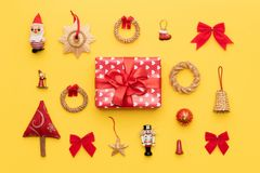 Christmas composition. Red christmas gift and many retro christmas ornaments isolated on bright yellow background. stock photo