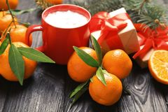 Christmas composition with ripe tangerines, cup of hot drink and gift box. On wooden table royalty free stock images