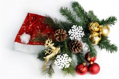 Christmas composition with Santa Claus hat, fir tree, cones, balls and snowflakes. Isolated white Royalty Free Stock Photos
