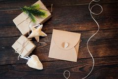 Christmas Composition set of gift kraft boxes, textile toys and cord frame on wooden background Stock Photography