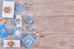 Christmas composition. Small blue and white gift boxes with bows, spirals of ribbons. Empty wooden background. Christmas composition. Small blue and white gift stock photography