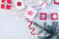 Christmas composition, small gift boxes with bows, spirals of ribbons and a branch of the Xmas tree. Blue background. Christmas composition, small gift boxes royalty free stock images