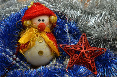 Christmas composition. Snowman. And a red star on a background of festive tinsel. New Year backgrounds Royalty Free Stock Photos