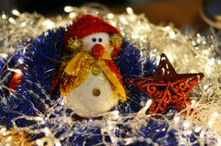 Christmas composition. Snowman. And a red star on a background of festive tinsel. New Year backgrounds Stock Photography