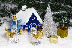 Christmas composition in a snowy forest. Christmas composition with a house in a snowy forest. In front of house are Snow Maiden and two angels. Around the house Royalty Free Stock Image