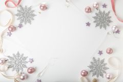 Christmas composition. Spruce branches, xmas tree, xmas pink decor holiday ball with ribbon on white background. stock photo