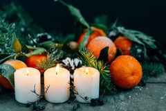 Christmas composition with Tangerines, Pine cones, Walnuts and Candles on Wooden Background, holiday decoration Stock Images