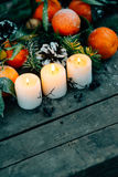 Christmas composition with Tangerines, Pine cones, Walnuts and Candles on Wooden Background, holiday decoration Royalty Free Stock Photography