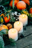 Christmas composition with Tangerines, Pine cones, Walnuts and Candles on Wooden Background, holiday decoration Stock Photo