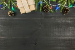 A Christmas composition. Top view, flat lay, copy space. Gift, spruce brunces, lights, cones royalty free stock images