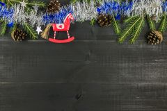 A Christmas composition. Top view, flat lay, copy space. Horse, spruce brunces, tinsel, cones royalty free stock image