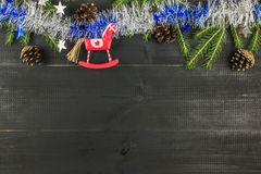A Christmas composition. Top view, flat lay, copy space. Horse, spruce brunces, tinsel, cones royalty free stock photography