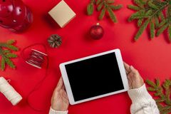 Christmas composition. Top view of tablet computer in woman hands. Christmas decoration and green fir branches on red stock photography