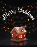 Christmas composition. Toy house on a black background blurry lights. Christmas, winter, new year concept royalty free stock photography