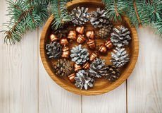 Christmas composition.Tree banches,white cones and golden acorns in the wooden plate stock image