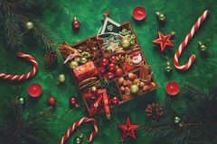 Christmas composition. Christmas tree and box with spices and toys on green wooden background royalty free stock photo