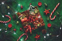 Christmas composition. Christmas tree and box with spices and toys on green wooden background. Festive mood. Flat lay. Top view stock photos