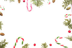 Christmas composition on white background. Xmas frame with candy canes, green thuja twigs, pine cones and red wild rose Stock Images