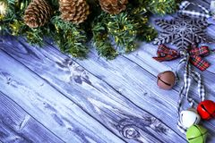 Christmas composition on wooden background red balls, gifts, and green Christmas tree branch with cones,burning candle. Foto Royalty Free Stock Image