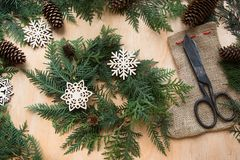 Preparation for Christmas holiday. Christmas composition of wreath, decor, dry orange, twigs and snowflakes. Woman prepare a wreat Royalty Free Stock Images
