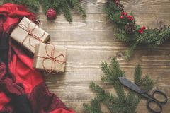 Christmas composition of wreath, gift boxes,checkered pleid on wooden board. Flat lay. Top view. Stock Photo
