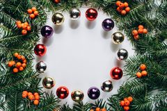 Christmas composition. Wreath made of christmas tree branches and red berries and Christmas toys on white background. stock photos
