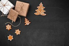 Christmas composition. Xmas cookies, gifts, festive decoration on black background. Flat lay, top view, with copy space. stock photo
