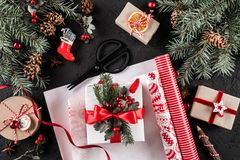 Christmas composition with xmas wrapping, Fir branches, gifts, pine cones, red decorations, scissors on holiday background. stock photos