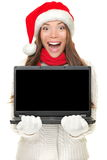 Christmas computer woman holding notebook. Excited wearing santa hat. Empty blank screen copy space for text. Beautiful young smiling female model isolated on Royalty Free Stock Photo