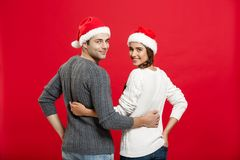 Christmas Concept - back view of portrait lovely young couple hugging over red background stock photo