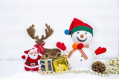 Santa Claus and gift box with christmas decoration over blurred bokeh on white background. Christmas concept background of snowman with happy Santa Claus and Stock Images
