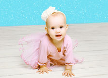 Christmas concept - beautiful baby little girl in pink dress crawls on floor Royalty Free Stock Photo
