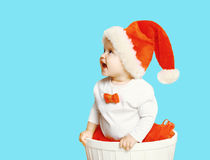Christmas concept - cheerful baby in santa red hat looking up Royalty Free Stock Image