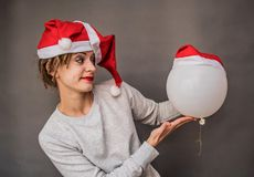 Young woman in santa hats puts a hat on a balloon stock photography