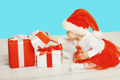 Christmas concept - child in santa red hat playing with a boxes gifts Stock Images