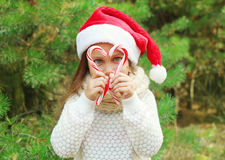 Christmas concept - child in santa red hat with sweet lollipop cane Stock Image