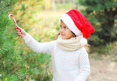 Christmas concept - child in santa red hat with sweet lollipop cane and tree Stock Photo