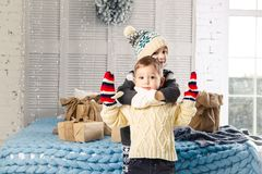 Christmas concept.Children brother and sister in embrace of the house in the bedroom near bed with boxes,gifts on back of the deco Stock Photography