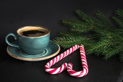 Christmas concept. Cup of coffee and candy cane in shape of heart on a black background with Christmas tree branches. Christmas concept. Blue mug of hot coffee Stock Image