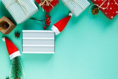 Christmas concept flat lay with empty lightbox. Warm, cozy winter clothing and Christmas decorations frame on green background stock images
