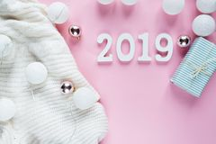 Christmas concept flat lay. Warm, cozy white winter clothing, 2019 number and Christmas decorations frame on pink royalty free stock photography