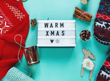 Christmas concept flat lay. Warm, cozy winter knitted clothing, light box and Christmas decorations on green background stock image