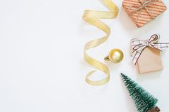Christmas concept. Gift box and pine tree and curling ribbon and bauble on white background royalty free stock images