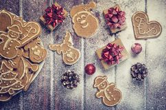 Christmas concept with gingerbread, gifts and snow. Sweet gingerbreads, gifts and baubles on a wooden table royalty free stock image