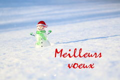 Christmas concept. Glass snowman on the snow, with the phrase Meilleurs voeux. Christmas concept. Glass snowman on the bright snow, with the phrase Meilleurs Royalty Free Stock Images