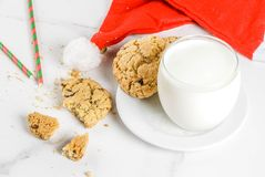 Milk and cookies for Santa Claus. Christmas concept, greeting card. Milk glass and cookies for Santa Claus with Santa`s hat on white marble background, copy Stock Photography